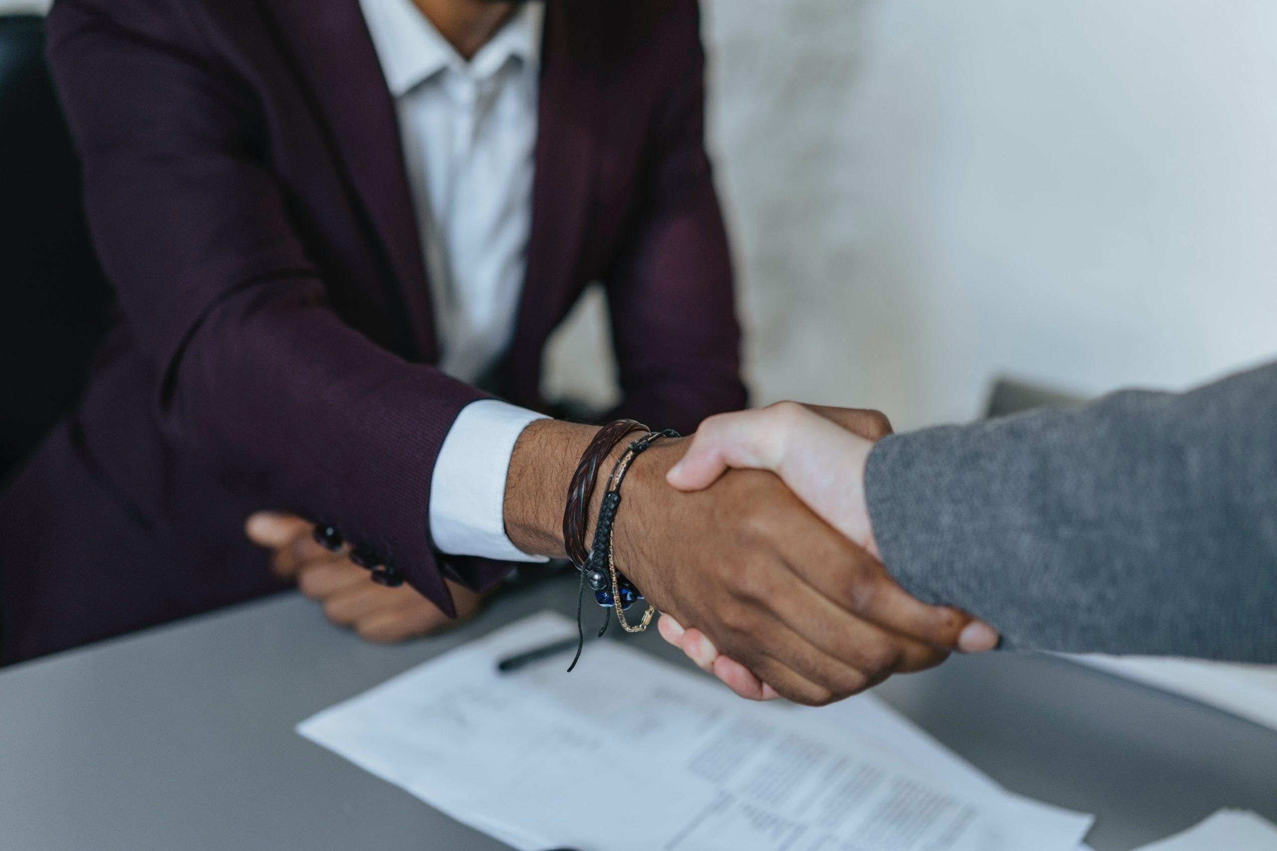 two men shaking hands over paperwork